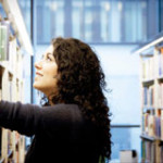 Student browsing the library's bookshelves
