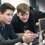 Photo of two students with a laptop